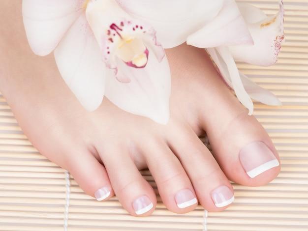 손톱에 흰색 프랑스 페디큐어와 여성 피트의 근접 촬영 사진. 스파 살롱에서. 다리 관리 개념