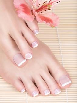 爪に白いフランスのペディキュアと女性の足のクローズアップ写真