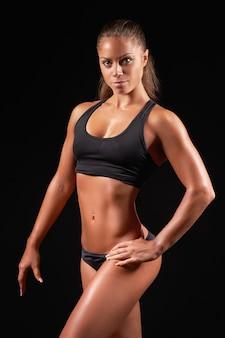暗い上に黒いスポーツウェアを着ているスポーツ女性の肖像画のクローズアップ写真