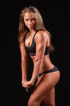 Крупным планом фото спортивного женского портрета в черной спортивной одежде на темноте