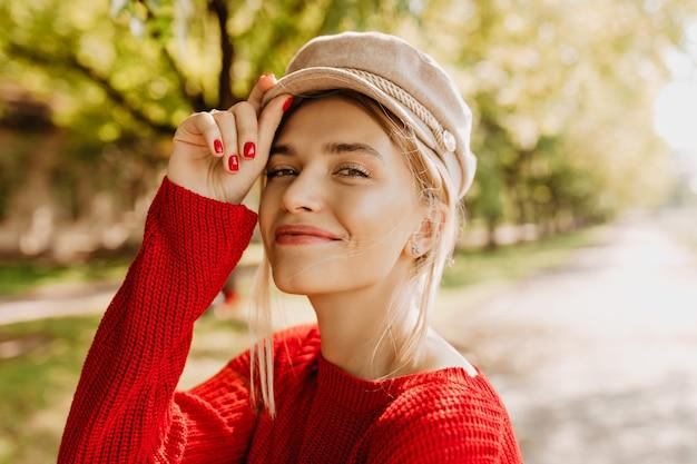 자연스러운 메이크업과 매력적인 미소로 멋진 금발 여자의 근접 촬영 사진. 멋진 세련된 스웨터에 사랑스러운 소녀