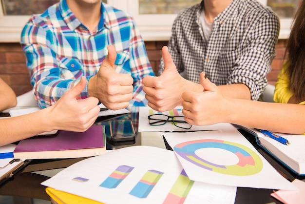 Крупным планом фото молодой группы показывает палец вверх, работая над бизнес-планом