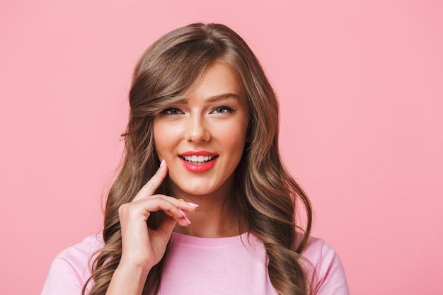 ピンクの背景に分離されたあなたを見ながら笑みを浮かべて長い巻き毛の茶色の髪を持つ愛らしいコンテンツ女性のクローズアップ写真