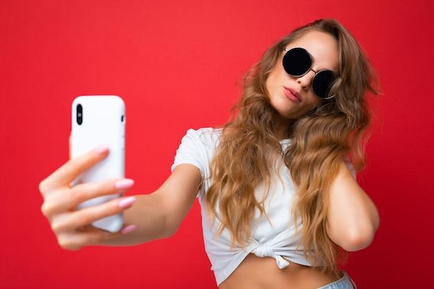 Крупным планом фото удивительной красивой молодой блондинки, держащей мобильный телефон, делающей селфи фото с помощью