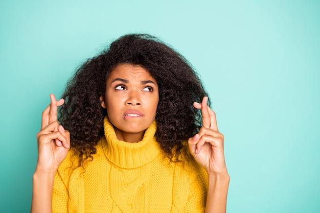 학교 시험 착용 노란색 니트 점퍼 절연 파란색 청록색 벽에 대해 걱정 입술을 물고 교차 손가락을 들고 놀라운 어두운 피부 아가씨의 근접 촬영 사진