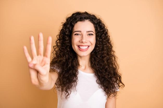 Крупным планом фото удивительной леди, поднимающей руку, показывающую, что четыре пальца начинают обратный отсчет, носить белый повседневный костюм, изолированный бежевый пастельный цвет фона