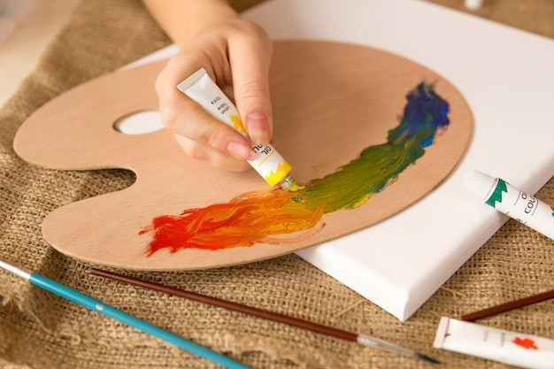 Крупным планом фото художника, сжимающего масляную краску на поддоне из тюбика