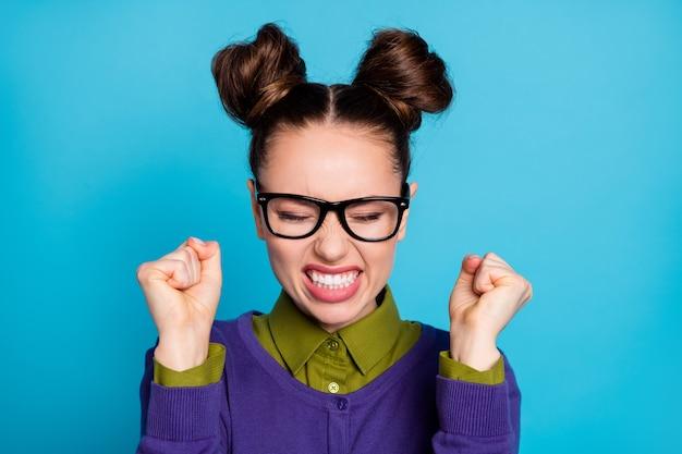 Крупным планом фото привлекательной сердитой студентки, смешные булочки с закрытыми глазами, поднять кулаки, ненавидеть себя, допустить ошибку на тестовом экзамене, носить характеристики, воротник рубашки, фиолетовый свитер, изолированный синий цвет фона