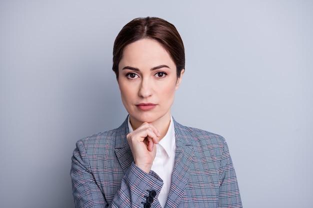 Крупным планом фото привлекательной бизнес-леди учительницы выглядят заинтересованными камера сосредоточила руку на подбородке, планируя будущий урок, носить клетчатый пиджак, белую рубашку, изолированный серый цвет фона