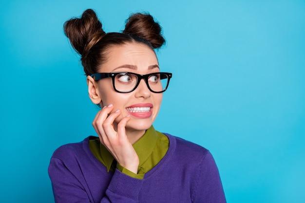 매력적인 미친 겁에 질린 학생 여성의 근접 촬영 사진 두 개의 재미있는 만두가 옆 빈 공간을 보고 실수로 셔츠 칼라 바이올렛 스웨터를 입고 파란색 배경을 착용했습니다.