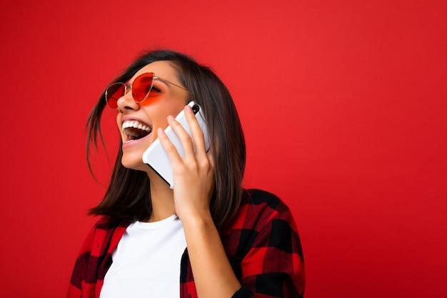 スタイリッシュな赤いシャツ白いtシャツと赤いサングラスを身に着けている魅力的な前向きな笑い若い黒髪の女性のクローズアップ写真見上げる携帯電話で通信する赤い背景の上に分離