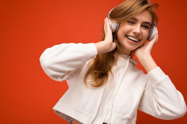 隔離された白いパーカーを着て魅力的なポジティブな笑顔の若いブロンドの女性のクローズアップ写真