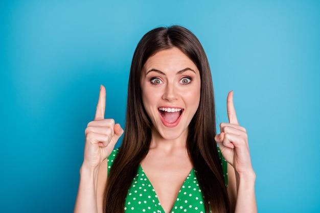 魅力的なきれいな女性のクローズアップ写真は、販売ショッピングバナーを示す空のスペースに直接指を大喜びしました緑の点線のタンクトップ一重項孤立した青い色の背景を着用してください