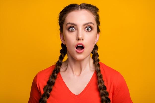 Крупным планом фото привлекательной шокированной дамы с двумя длинными косами с открытым ртом