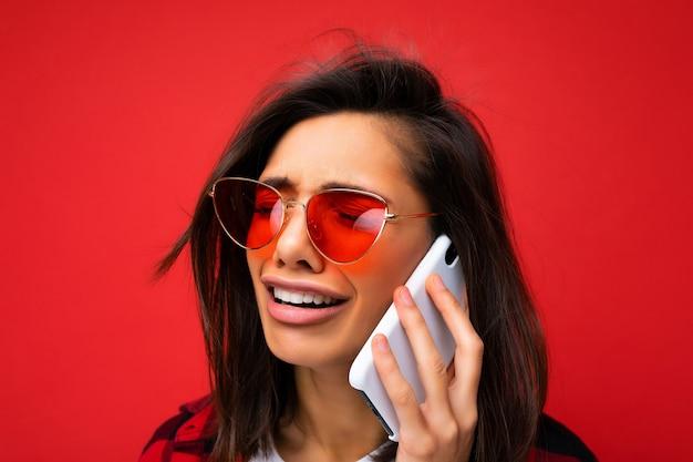 携帯電話で通信する赤い背景の上に分離されたスタイリッシュな赤いシャツ白いtシャツと赤いサングラスを身に着けている魅力的な動揺泣いている若い黒髪の女性のクローズアップ写真