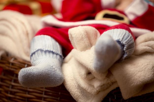 Фото крупного плана младенца, лежащего в голубых шерстяных носках. рождественское понятие