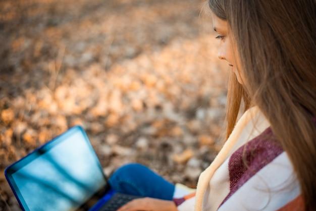 공원에서 노트북 작업을 하는 아름다운 소녀의 근접 촬영 사진