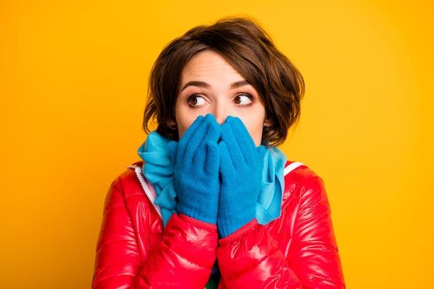 顔の表情を隠している美しい女性のクローズアップ写真は口に腕を保持します空のスペースを見ておびえた着用カジュアルな赤いオーバーコート青い手袋