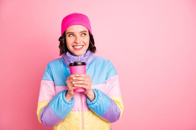 뜨거운 손을 잡고 아름 다운 아가씨의 근접 촬영 사진 음료를 꺼내 따뜻한 컬러 코트 절연 분홍색 배경을 착용
