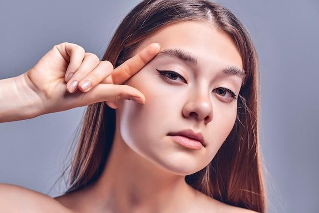 美しい女性のクローズアップ写真ヌード裸の肩ふっくらとした形の唇魅力的な外観指チェック眉毛アイラインしわのない顔孤立した灰色の背景