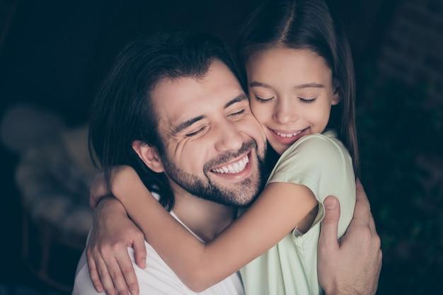 夢のような笑顔の目を閉じて抱き締める美しい小さな愛らしい女の子ハンサムな若いパパのクローズアップ写真は、週末の時間を家庭的な家庭的な雰囲気の家の部屋の屋内で過ごす