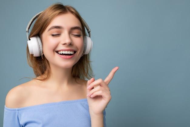 青いクロップトップを身に着けている美しいポジティブな笑顔の若いブロンドの女性のクローズアップ写真