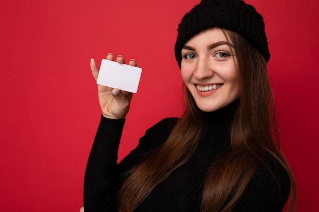 검은 스웨터와 모자를 쓰고 아름 다운 미소 젊은 갈색 머리 여자의 근접 촬영 사진