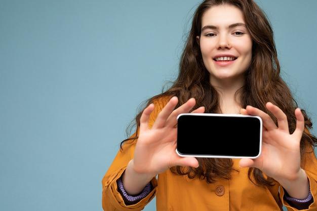 Крупным планом фото красивой улыбающейся молодой женщины, хорошо выглядящей в повседневной стильной одежде, стоящей