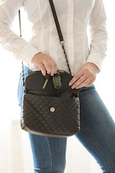 ハンドバッグから車のキーを取る美しい女性のクローズ アップ写真