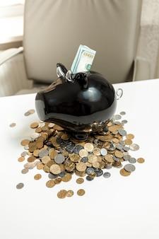 흰색 테이블에 동전 더미에 서있는 검은 돼지 저금통의 근접 촬영 사진