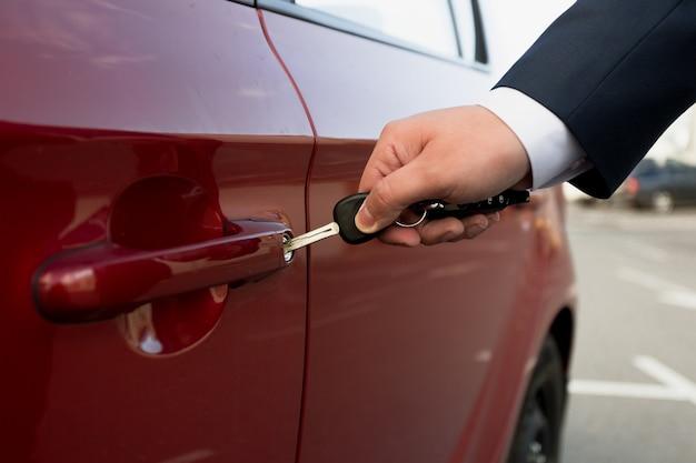 キーで駐車中の車を開くビジネスマンのクローズアップ写真