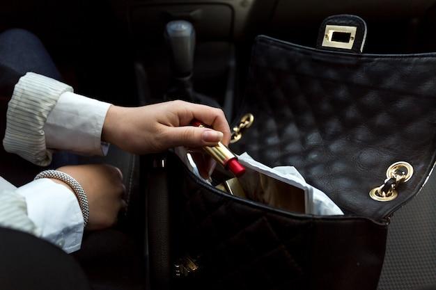 핸드백에서 빨간 립스틱을 복용하는 사업가의 근접 촬영 사진