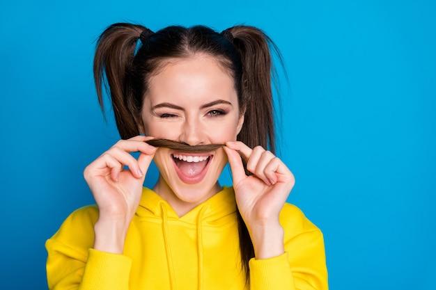 魅力的なきれいな女性のクローズアップ写真は、男の遊び心のある服のように偽の口ひげをまばたきする尾を保持しますカジュアルな黄色のパーカープルオーバー分離された明るい青色の背景