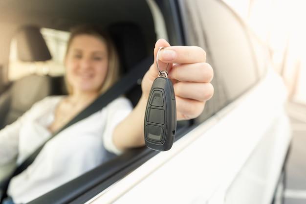 쾌활한 젊은 여자가 차를 운전하고 차 열쇠를 보여주는 근접 촬영 사진