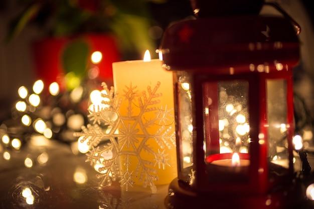 クリスマス ライト、燃えているろうそく、テーブルの上のビンテージ ランタンのクローズ アップ写真