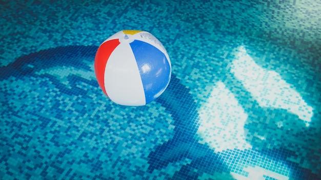 スイミングプールの水面に浮かぶカラフルなストライプのインフレータブルビーチボールのクローズアップ写真