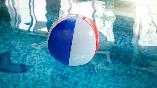 Крупным планом фото красочных полосатых надувных пляжных мячей, плавающих на поверхности воды в бассейне