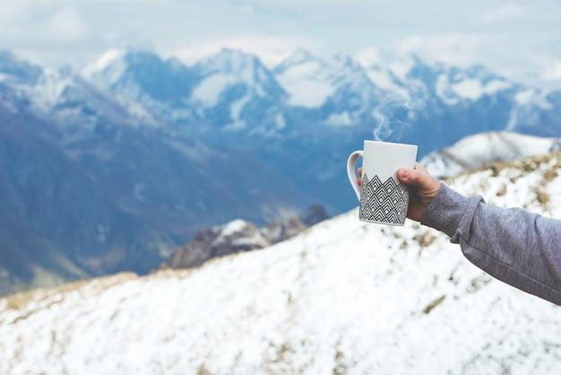 焦点の合っていない山の景色を渡る旅行者の手にお茶とカップのクローズアップ写真。若い観光客の女性がカップから温かい飲み物を飲み、山の景色を楽しんでいます。トレッキングのコンセプト。