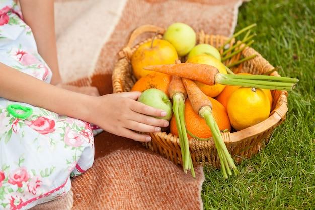 Крупным планом фото милой девушки на пикнике с корзиной фруктов и овощей
