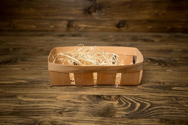 Крупным планом фото пустой маленькой корзины, покрытой соломой, лежащей на старом деревянном столе