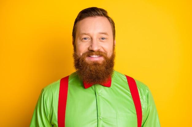 Крупным планом фото возбужденного счастливого рыжего парня с зубастым сияющим улыбающимся элегантным взглядом в ярко-зеленой рубашке с красными подтяжками и галстуком-бабочкой, изолированные яркие цвета
