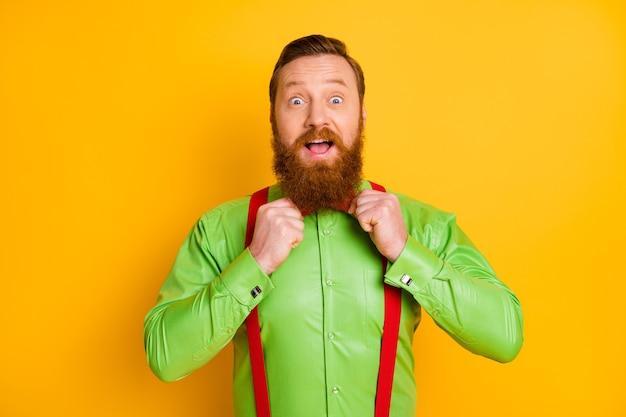 Крупным планом фото возбужденного рыжего парня элегантная стильная одежда, поправляющая галстук, зеркало, подготовка вечеринки, ярко-зеленая рубашка, красные подтяжки, галстук-бабочка, изолированные яркие цвета