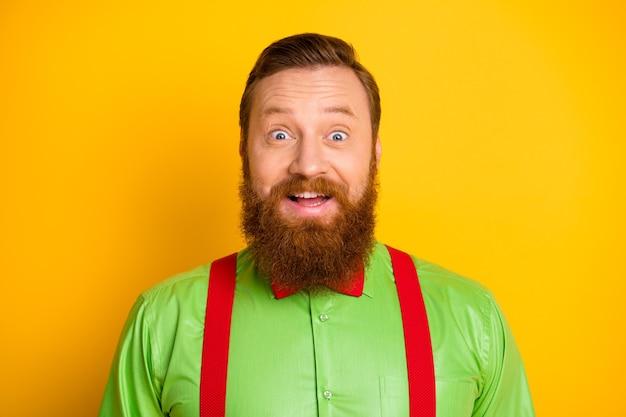 Крупным планом фото возбужденного рыжеволосого привлекательного парня с открытым ртом слушать хорошие новости сумасшедшее выражение лица носить зеленую рубашку подтяжки галстук-бабочку изолированный цвет блеска