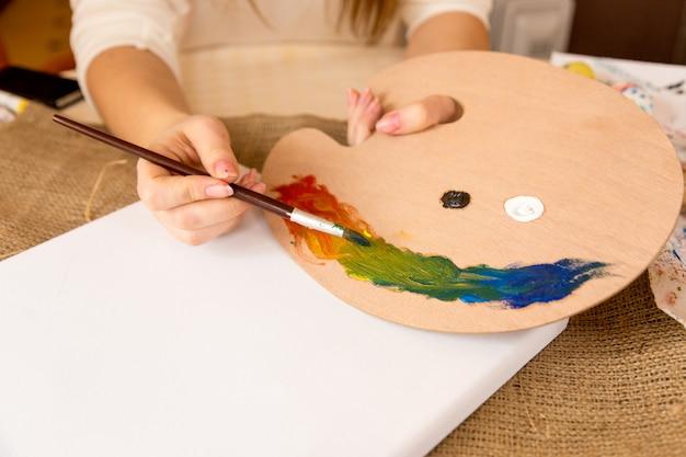 Крупным планом фото художницы, смешивающей масляные краски на деревянном поддоне