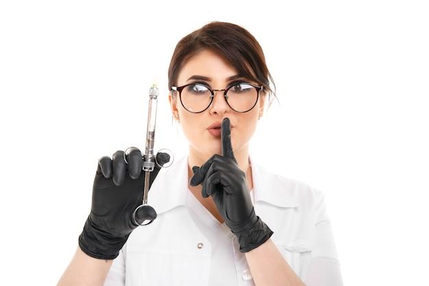 검은 장갑을 끼고 안경을 쓴 여성 치과 의사의 근접 촬영 사진과 가지 backgrownd 위에 격리된 치과 직원이 있습니다.