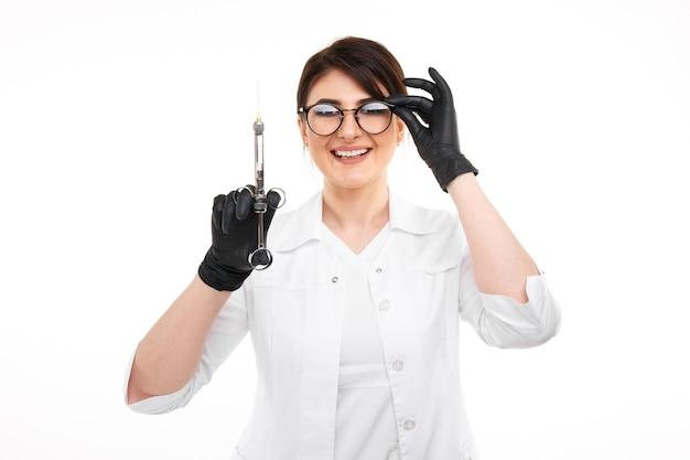 검은 장갑을 끼고 안경을 쓴 여성 치과 의사의 근접 촬영 사진.