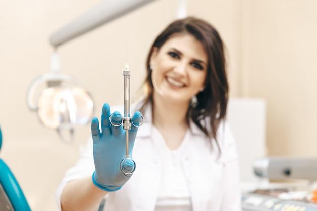 구강 주사기를 들고 치과 방에서 여성 치과 의사의 근접 촬영 사진.