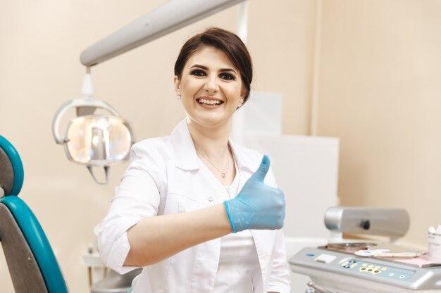엄지손가락을 보여주는 치과 방에서 여성 치과 의사의 근접 촬영 사진.