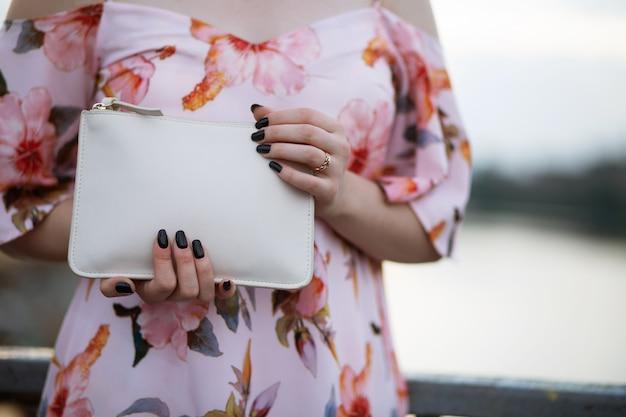 白い革の財布を持っている女性の手のクローズアップ写真。テキスト用のスペース