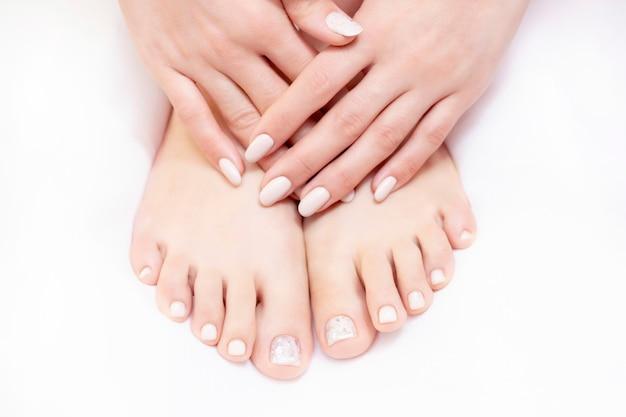 Фото крупного плана женских ног на белом полотенце в салоне курорта на процедуре по pedicure и маникюра. ню цвета.